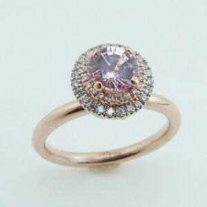 14 karat rose and white gold ring featuring a 0.725ct light pink sapphire accented by a double halo of 0.20ctw round brilliant cut diamonds.