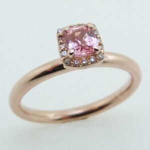 14 karat rose gold ring featuring a 0.40ct Padparadscha sapphire and a halo of round brilliant cut diamonds.