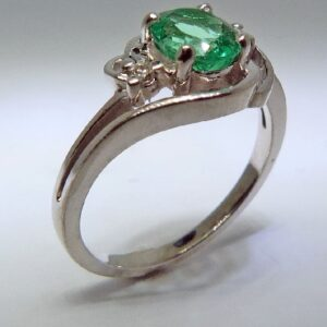 14 karat white gold ring set with a 0.815ct emerald and 0.04ctw round brilliant cut diamonds.