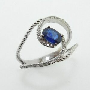 14 karat ring featuring an oval sapphire accented with diamonds in a modern, open twist design.