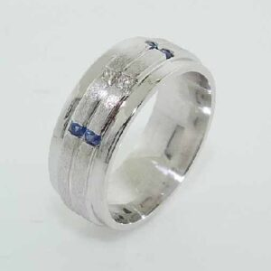 14K White gold custom men's band by Studio Tzela featuring 2 channel set princess cut diamonds, 0.09cttw, SI1, G/H, and 4 round brilliant cut blue sapphires, 0.168cttw.