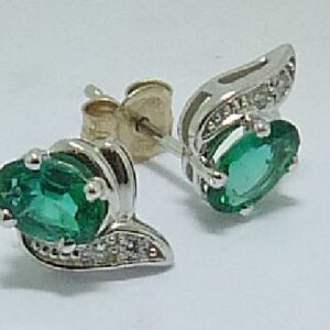 14 karat white gold stud earrings set with 2 = 0.621ctw emeralds and accented with 4 = 0.031ctw of round brilliant cut diamonds.