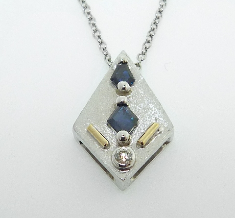 14k white gold pendant featuring two sapphires with a total weight of 0.45ct and a bezel set 0.044ct round brilliant cut diamond.