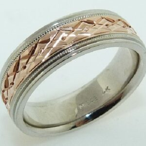 14 Karat rose & white gold 7mm flat two-tone band with an engraved intersecting diamond pattern in the rose gold centre accented with milgrain detail and polished white gold edges.