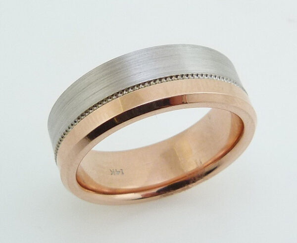 14 Karat rose & white gold 7.5mm flat two-tone band with a stainless and polished texture with milgrain detail and polished rose gold sleeve.
