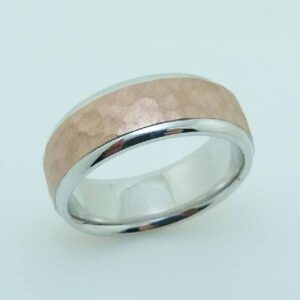 14K White and rose gold men's domed 8 mm band with white gold in polished edges and rose gold hammered texture with stainless finish centre.