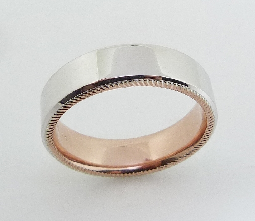 14 Karat rose & white gold 6.5mm flat band with a polished white gold topside and accented with a rose gold sleeve and coin detail edges.