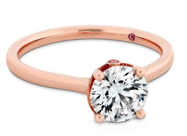 18 karat rose gold Sloane solitaire engagement ring by Hayley Paige for Hearts on Fire. This stunning ring is available in white, yellow and rose gold as well as platinum. Each ring by Hayley Paige for Hearts on Fire features a pink sapphire (in Hayley's favourite shade of pink) on the inside of the band. Priced without a center gemstone. Let us find you the perfect center that fits your tastes and budget!
