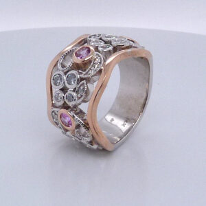 14 karat white and rose gold floral design ring set with 0.59ctw of pink sapphires and 24 = 0.678ctw F/G, VS-SI round brilliant cut diamonds. This stunning ring has milgrain engraving and is a custom design by David.