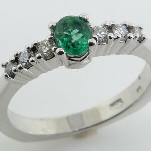 14 karat white gold ring set with a 0.27ct oval emerald and accented with 6 = 0.142ctw G/H, SI round brilliant cut diamonds
