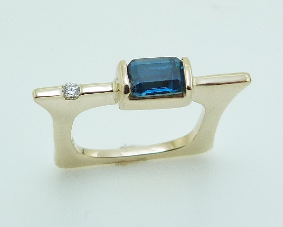 14 karat yellow gold modern design ring featuring a 0.555ct blue zircon and a 0.015ct round brilliant cut diamond.