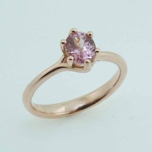A 14 karat rose gold solitaire ring, showcasing a 0.805 carat round brilliant cut Lotus Garnet. This piece is perfect to represent January birthdays and 2nd anniversaries.