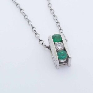 14K white gold pendant set with a 0.10ct I/J, SI2, excellent cut round brilliant cut diamond and 2 emeralds, 0.202cttw.