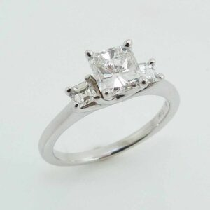 14K White gold engagement ring, set with two G, VS Carre (square) diamonds totaling 0.27 carats and set in the center with one 1.012 carat H, SI1 good-very good cut radiant cut diamond.