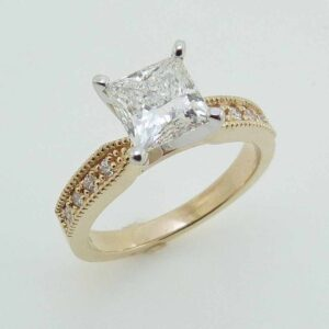 14k yellow and white gold engagement ring with milgrain detail on the band set with a 1.38ct I VS1 square modified brilliant cut diamond by FireMark and accented with 8 pave set, round brilliant cut diamonds, 0.114cttw, excellent cut, F/G, SI1.