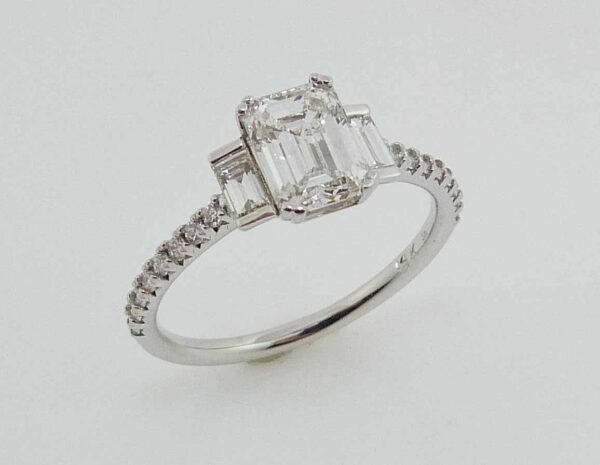 14 karat white gold solitaire engagement ring featuring a 1.02ct G, VS1 emerald cut diamond and accented by 2 = 0.16cttw G/H, VS-SI, 16 = 0.16cttw G/H, VS-SI round brilliant cut diamonds.