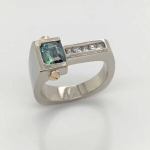 14K white and yellow gold custom lady's ring by Studio Tzela with bezel set with a 1.148ct emerald cut blue/green sapphire and 5 = 0.15cttw princess cut diamonds.