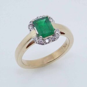 14 karat white and yellow gold halo ring set with a 0.803ct Emerald accented by 12 = 0.144ctw round brilliant cut diamonds. Emerald is the birthstone for May.