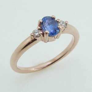 14 karat rose gold ring featuring a 0.618ct oval sapphire accented by 2 = 0.073ct G/H, SI, round brilliant cut diamonds.