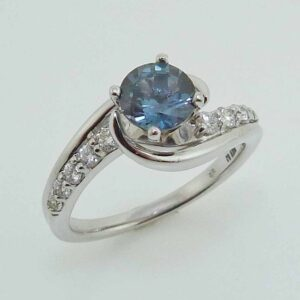 14K white gold ring set with a 1.08ct blue/green sapphire and accented with 10 very good cut, round brilliant cut diamonds, 0.27cttw, G/H, SI1-2.