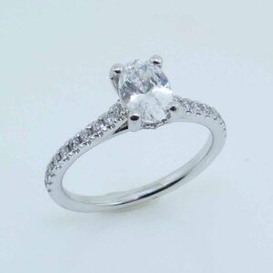 Lady's diamond hidden halo engagement ring in 14K white gold, set with a 7x5 oval CZ in the center and accented with thirty G-H SI1 round brilliant cut diamonds totaling 0.23 carats.