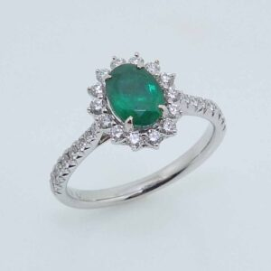 14 karat white gold halo ring set with a 0.69ct Emerald accented by 30 = 0.41ctw round brilliant cut diamonds.