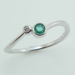 14 karat white gold bypass style band bezel set with a 0.09ct emerald and a 0.014ct G/H, I1 round brilliant cut diamond.