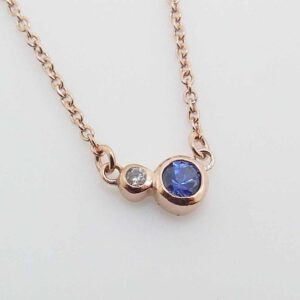 "14K rose gold pendant bezel set with a 0.12ct Sapphire and a 0.0.014ct G/H, I1 round brilliant cut diamond.  This pendant comes with a 14k rose gold 18"" chain."