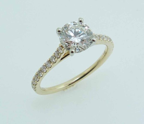 14K yellow and white gold engagement ring with an ideal cut, round brilliant cut Hearts On Fire diamond centre, 0.928 carat, I, VS1, and 26 round brilliant cut diamonds on the band, 0.28cttw, G/H.