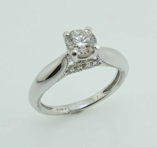 14 karat white engagement ring featuring a 0.64ct H, VS2 round brilliant cut diamond set in an 18KW 4 claw head accented by 0.07ctw of round brilliant cut diamonds.