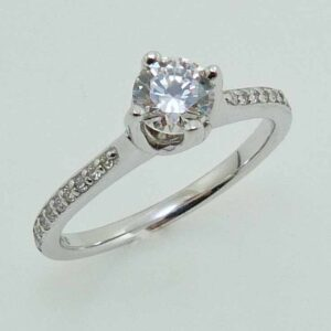 14K White gold solitaire engagement ring with an offset centre setting 0.5ct CZ and 20 round brilliant cut diamonds, 0.12cttw, G/H, SI. Priced without a center gemstone. Let us find you the perfect center that fits your tastes and budget!