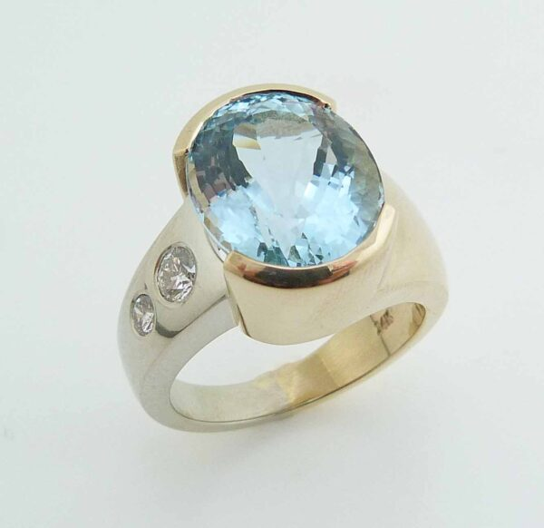 14 karat white and yellow gold ring set with a 7.089ct oval cut Aquamarine and accented by 0.151ct G/H, SI round brilliant cut diamond and a 0.071ct G/H, SI round brilliant cut diamond. This beautiful ring is a custom Design by David.
