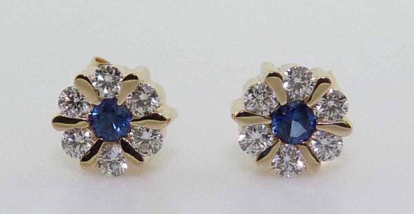 14K Yellow gold earring cluster set with two round blue sapphire totaling 0.19 carats and twelve round brilliant cut diamonds totaling 0.37 carats.