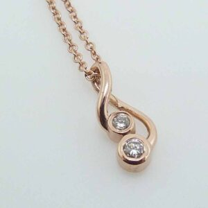 14K rose gold pendant set with 2 round brilliant cut diamonds, 0.06cttw H, SI1-2 on a 14k rose gold adjustable light cable chain.