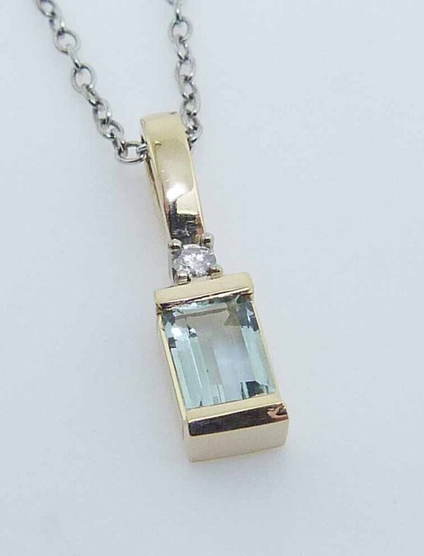 14K white and yellow gold custom pendant by Studio Tzela featuring a 0.82ct Aquamarine, and accented with a 0.04ct round brilliant cut diamond.
