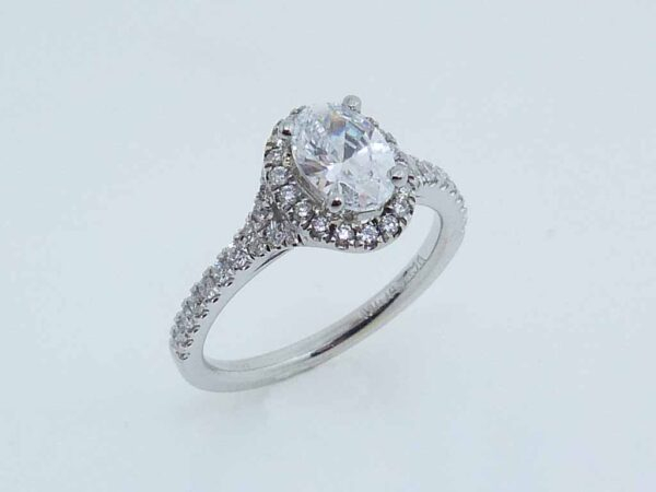 14 karat white split-shank oval halo engagement ring accented by 44 = 0.32cttw G/H, VS-SI, round brilliant cut diamonds.