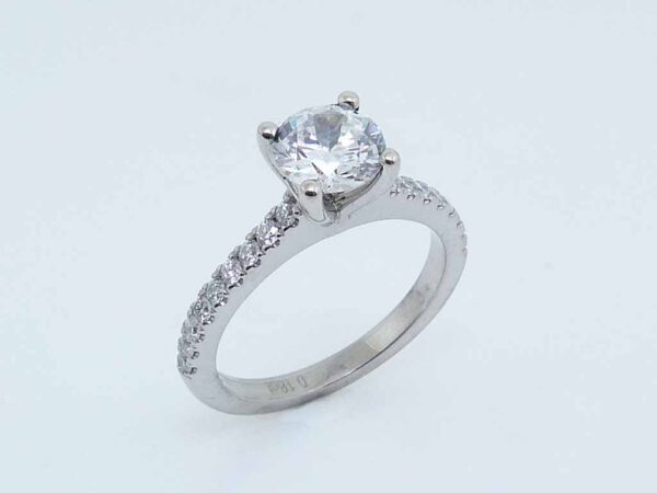 14 karat white gold solitaire engagement ring featuring 0.25ctw G/H, VS-SI round brilliant cut diamonds down the band.
