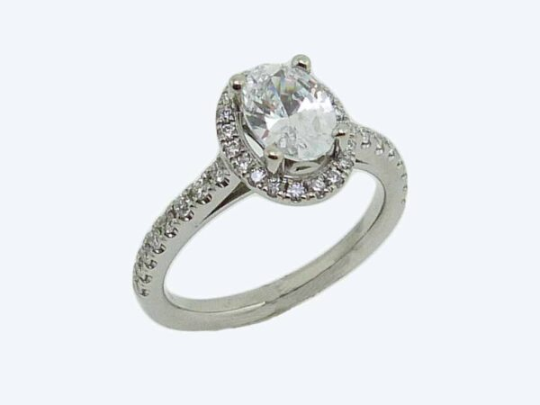 18 karat white oval halo engagement ring accented by 36 = 0.75cttw G/H, VS-SI, round brilliant cut diamonds.