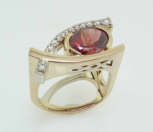 14K White and yellow gold custom Studio Tzela lady's ring set with a 2.34 carat oval rhodolite garnet and 12 very good cut, round brilliant cut diamonds, 0.19cttw, I/J, SI1-2.