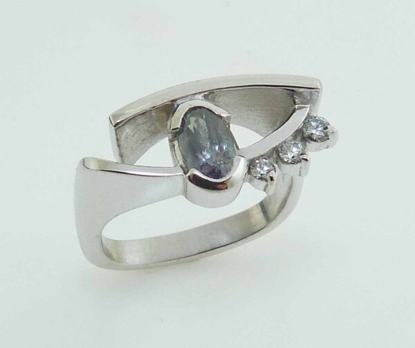 Lady's white gold custom ring semi bezel set with one 0.85 carat oval Alexandrite and claw-set with three F-G SI+ excellent cut round brilliant cut diamonds, totaling 0.113 carats.