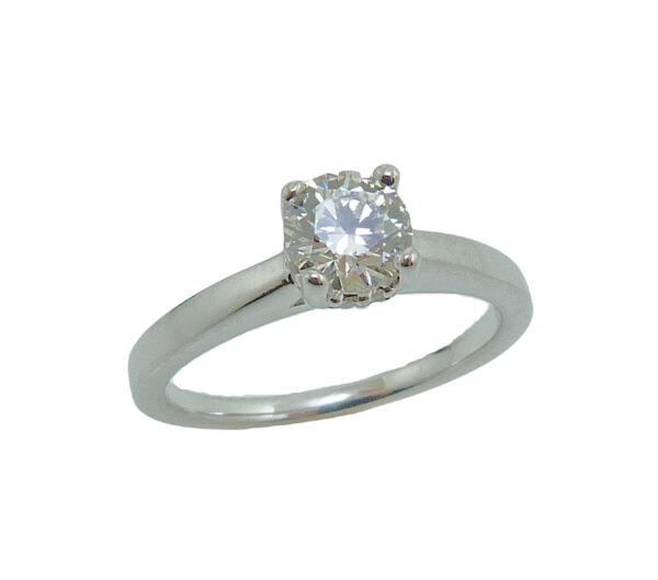 14 karat white gold solitaire engagement ring with a 4 prong head featuring a 0.57ct, I, VS2 round brilliant cut diamond by Hearts on Fire. This solitaire also features a hidden halo with 0.50cttw G/H, SI1 round brilliant cut diamonds.