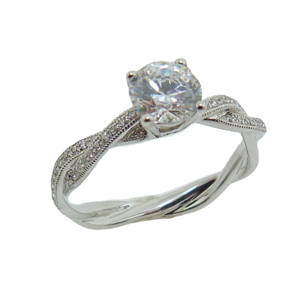 14K White gold engagement ring with pave set diamond twist shank and milgrain detail on the edge. Set with 1 carat round CZ centre and 40 round brilliant cut diamonds, 0.10cttw, G/H, VS-SI. Priced without a center gemstone. Let us find you the perfect center that fits your tastes and budget!