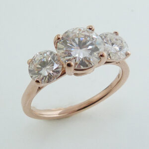 14K rose gold engagement ring claw set with one 6.5 mm and two 5 mm round G-I colour moissanites.