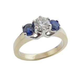 14K White and yellow gold engagement ring claw set with a 0.51 carat I, I1 very good cut, round brilliant cut diamond and accented on each side with two round blue sapphires, totalling 0.98 carat.