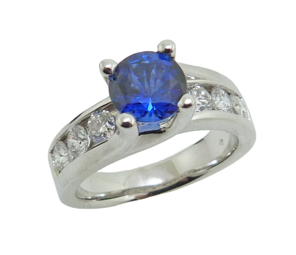14 karat white gold ring featuring a 1.32ct sapphire accented by 10 = 0.90ct G/H, VS2-SI, round brilliant cut diamonds. Sapphire is the birthstone for September.