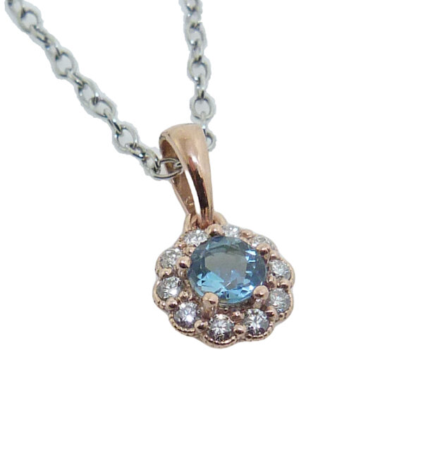 14 Rose gold floral halo pendant set with a 4mm aquamarine and accented with 0.125cttw H, SI1-2, round brilliant cut diamonds. Aquamarine is the birthstone for March.