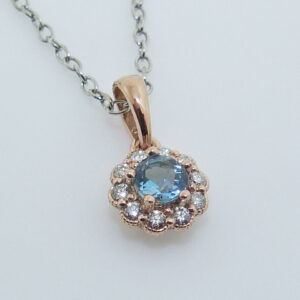 14 rose gold floral halo pendant set with a 4mm aquamarine and accented with 0.125cttw H, SI1-2, round brilliant cut diamonds.