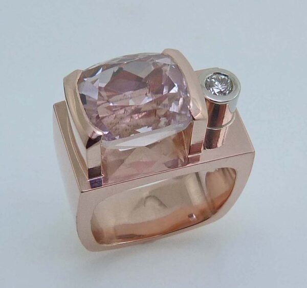 Lady's custom ring in 14K rose gold, semi-bezel set with 9.27 carat cushion cut morganite and accented with a bezel set 0.151 carat, G, SI1, very good cut, round brilliant cut diamond.