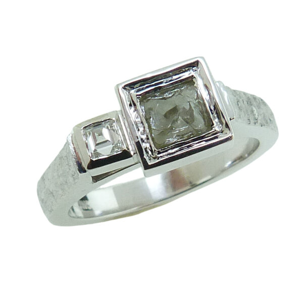14K white gold ring bezel set with 0.65 carat rough (uncut) diamond and accented with 0.072 carat carre' cut inversely set, F-G, VS.