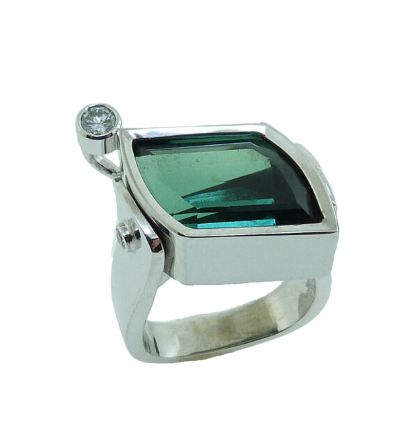 19 karat white gold coloured gemstone ring by Studio Tzela bezel set with one 7.90 carat Green Tourmaline and accented with a round brilliant cut diamond, 0.14 cttw, SI2, H/I and 2 bezel set round brilliant cut diamonds, 0.04cttw, SI.